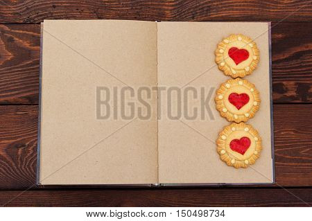Open notebook with blank pages on wooden background. Cookies in the shape of hearts. Diary for girls. Copy space. Christmas homemade cookies. Cookies in the form of hearts.