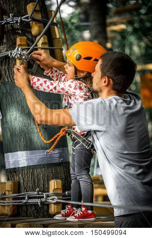 sports happy child with father climbs over the ropes beautiful girl in the outfit climbing fun in the forest on ropes and different obstacles family friendly
