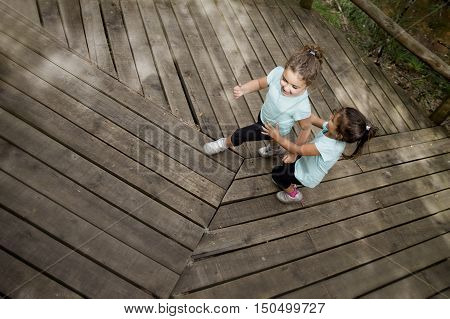 Wide angle of two smiling sisters in blue t-shirt playing and running on wooden path in park