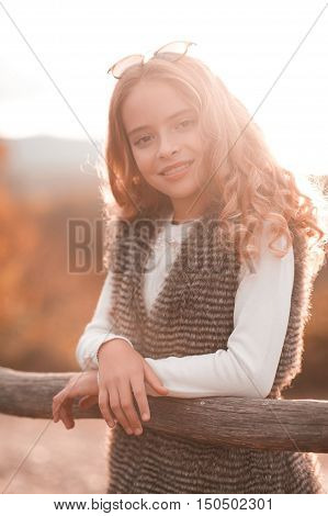Smiling teen girl 13-14 year old posing in sun light outdoors wearing casual autumn clothes. Looking at camera.