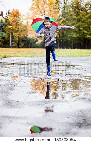 Boy In Rubber Blue Rainboots Jumping To Dirty Puddle