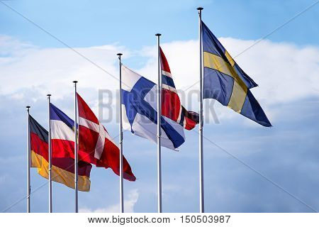 flags of the nordic european countries sweden norway finland denmark schleswig-holstein and germany in the wind against the blue sky