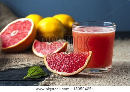 Glass of freshly squeezed grape fruit juice on burlap napkin on the background of grapefruit slices and lemons. Drink for dieting. Focus on slice.