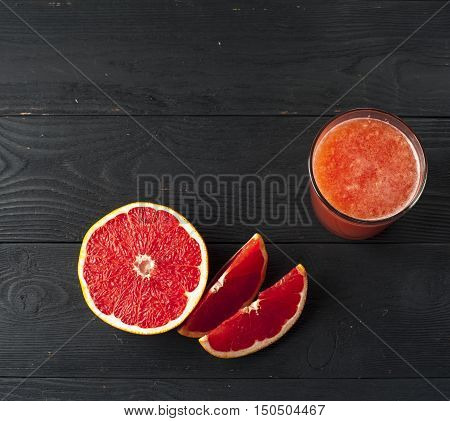 Glass of freshly squeezed grapefruit juice and grapefruit slices on wooden table. Drink for dieting.
