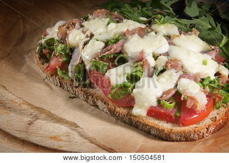 gratinated bread with tomato spring onions bacon and mozzarella cheese quick and easy pizzatoast on baking paper and a rustic wooden board selected focus