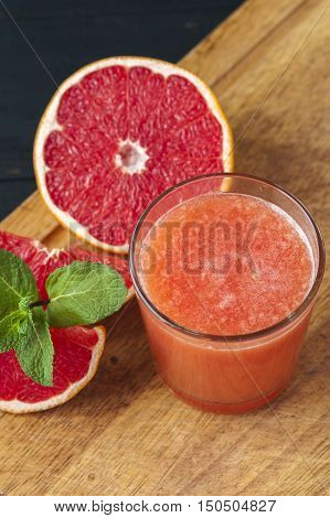 Glass of freshly squeezed grapefruit juice on wooden table. Drink for dieting.