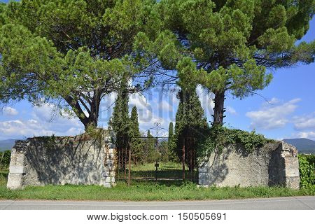 An old historic stone gate and what remains of the wall in rural north east Italy