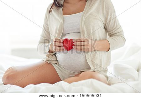 pregnancy, love, people and expectation concept - close up of pregnant woman with red heart in bed at home bedroom
