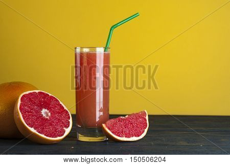 Glass of fresh grapefruit juice and grapefruits on wooden table. Drink for dieting.