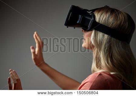 technology, augmented reality, entertainment and people concept - happy young woman with virtual reality headset or 3d glasses touching something invisible