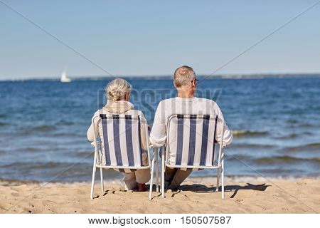 family, old age, travel, tourism and people concept - happy senior couple sitting on deck chairs on summer beach
