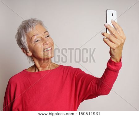 happy smiling mature woman in her sixties taking a selfie or self portrait with her smartphone