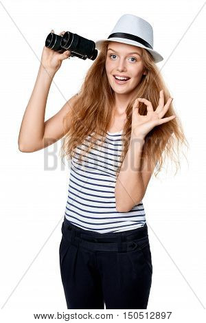 Happy emotional young beautiful teen female in striped tee and white straw fedora hat holding binoculars and looking at camera and gesturing OK, over white background
