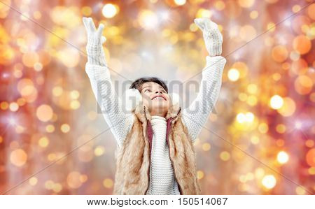 winter, people, christmas and happiness concept - happy little girl wearing earmuffs and gloves over holidays lights background