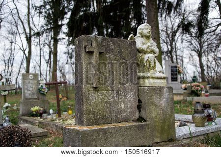 TVRDOMESTICE SLOVAKIA - 12.3. 2016: Graves tombstones and crucifixes on traditional cemetery. Statue of an angel on old tomb stone in graveyard. Gravestones in small village