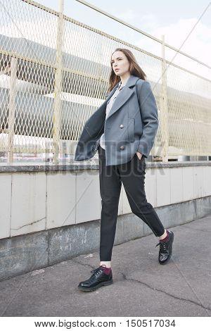 Young Fashion Woman In Grey Coat Walking In Street