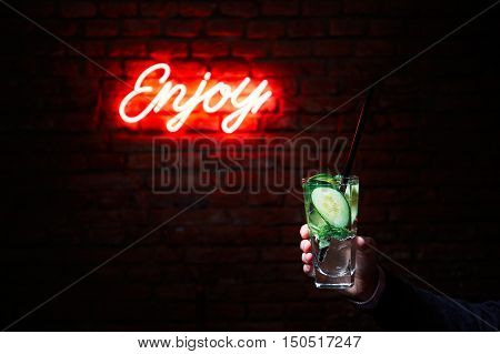 Hand of the young man with drink (barman or guest) in the bar in front of the brick wall with the inscription enjoy.