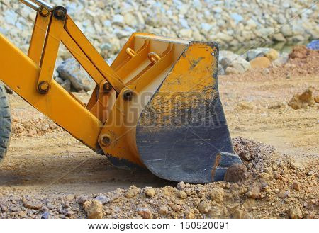 Bucket of front-end loader pushing dirt while working on a new road near Songkhla, Thailand