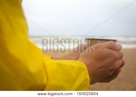 Men in yellow raincoat on the beach over the stormy sea holding a cup of hot drink