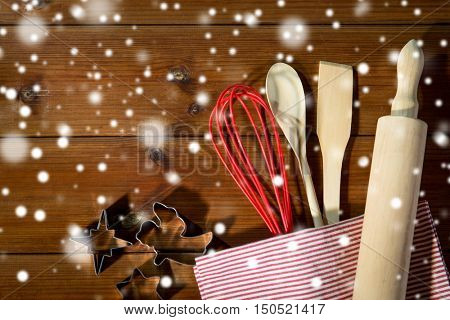 baking, cooking, christmas and home kitchen concept - close up of kitchenware set for baking gingerbread on wooden board from top