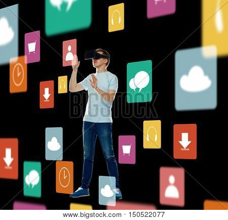 3d technology, augmented reality, gaming, cyberspace and people concept - happy young man in virtual reality headset or 3d glasses with menu icons over black background