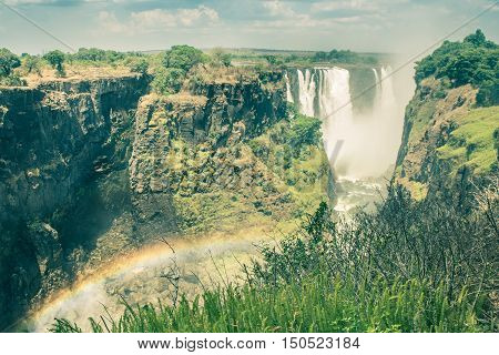 Side view of Victoria Waterfalls with rainbow natural effect - World famous nature wonder of Zimbabwe and Africa continent - Vintage filtered look