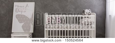 Panoramic photo of a white baby crib standing by a grey stucco wall