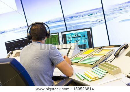 Sofia Bulgaria - September 12 2016: An air traffic controller is directing flights during a working day at Bullgaria's Air Traffic Services Authority control center room. Talking with the pilot.