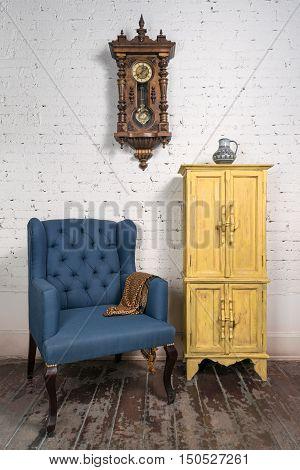 Still life of vintage blue armchair yellow cupboard pendulum clock and orange ornate scarf in studio