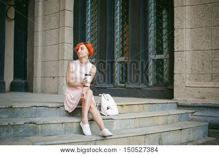 Drinks Coffee From A Cup. Woman With Dyed Red Hair In A Pale Pink Dress Drinking Coffee, Holding A P