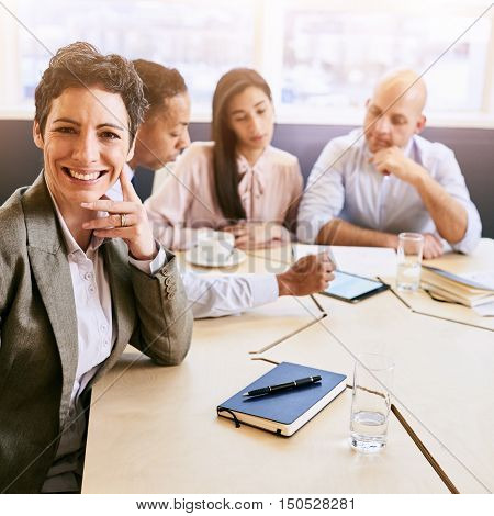 Single out of a mature businesswoman seated in front of her three colleagues sitting behind her still busy working as she smiles confidently at the camera.