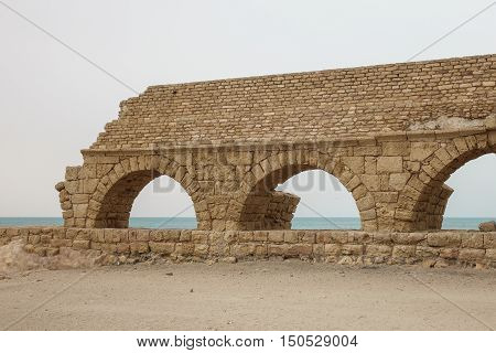 Ruined Roman aqueduct in Caesarea Israel at Midday