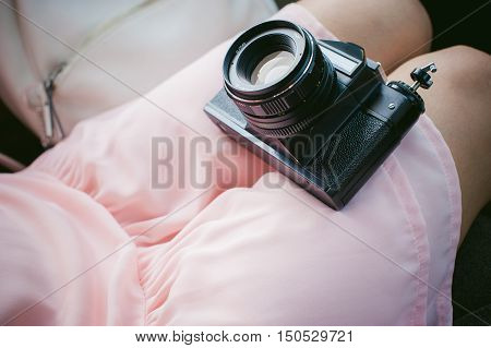 Girl With Vintage Camera In His Hands. Sitting In The Car, The Girl In A Pink Dress Holding A Retro