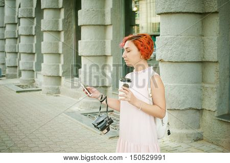 Girl Talking On The Phone, Drinking Coffee. Woman With Dyed Red Hair In A Pale Pink Dress With Backp