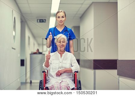 medicine, age, support, health care and people concept - nurse taking senior woman patient in wheelchair and showing thumbs up at hospital corridor