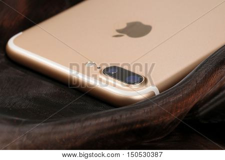 Koszalin, Poland - October 06, 2016: Golden iPhone 7 Plus on abstract background. Devices displaying the applications on the home screen. The iPhone 7 Plus is smart phone with multi touch screen produced by Apple Computer, Inc.