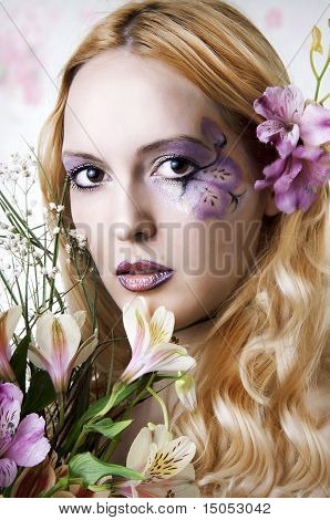 Young Woman With Makeup And Exotic Flowers