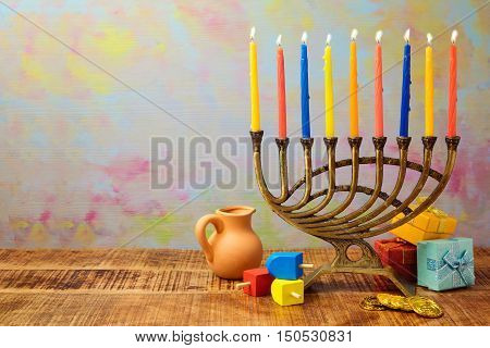 Jewish holiday Hanukkah celebration with menorah dreidel gifts and oil jug on wooden table