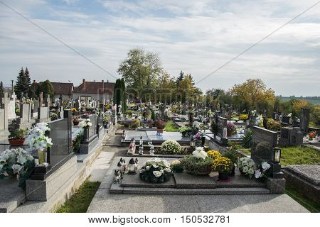 PRASICE SLOVAKIA - 29.10.2015: Graves tombstones and crucifixes on traditional cemetery in small village. Votive candles lantern and flowers on tomb stones in graveyard. All Saints' Day.All Souls'Day