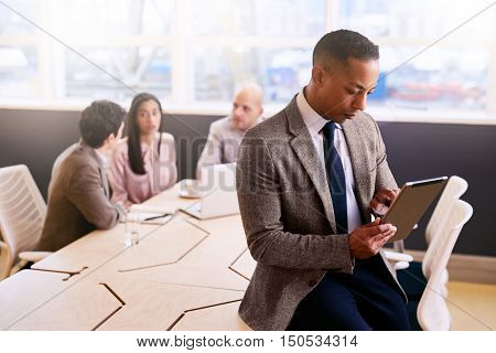 Businessman sitting on the edge of the board room table holding and using an electronic tablet with three colleagues seated at the table behind him.