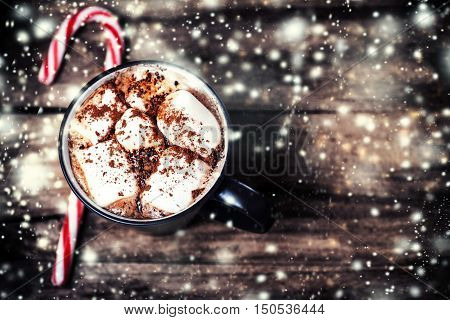 Hot Chocolate with marshmallows and candy stick traditional beverage for winter time vintage toning. Christmas decorations Xmas Card
