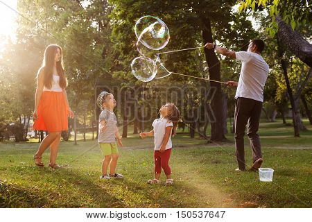 Family playing with large bubbles in backyard