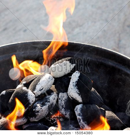 A grill with charcoal and flames
