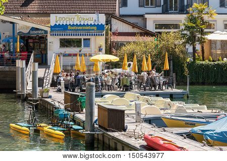 WEGGIS SWITZERLAND - MAY 05 2016: Unidentified guests of the bistro bar enjoys food and drinks. Guests sit at tables arranged on the platform at the Jetty on the Lake Lucerne