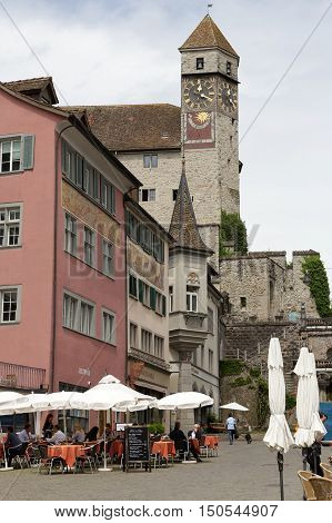 RAPPERSWIL SWITZERLAND - MAY 10 2016: Clock tower towering over the buildings of the city can be seen from the side of town square. Several people can be seen in a distance.