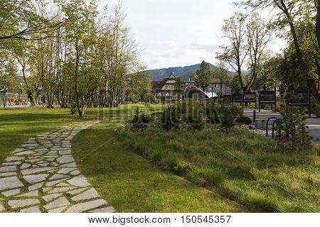 ZAKOPANE POLAND - SEPTEMBER 23 2016: Alley runs through the city park named Marshal Jozef Pilsudski the revitalization of the park was completed in 2013