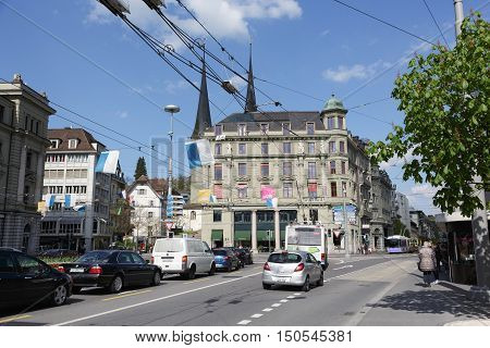 LUCERNE SWITZERLAND - MAY 04 2016: Cityscape includes a massive residential building with decorative facade. On the street a few cars in traffic and few people can be seen in the distance