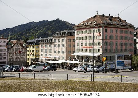EINSIEDELN SWITZERLAND - MAY 09 2016: Colorful facades of buildings and cars on a street shows the town that is often visited by pilgrims and tourists because of the widely known Einsiedeln Abbey