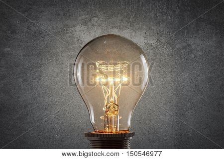 Glowing light bulb over grunge wall. Idea concept