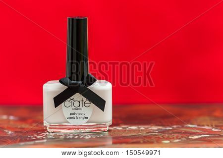 WREXHAM UK - OCTOBER 01 2016: Bottle of pale pink Ciate nail polish on a decorative table with a red background.